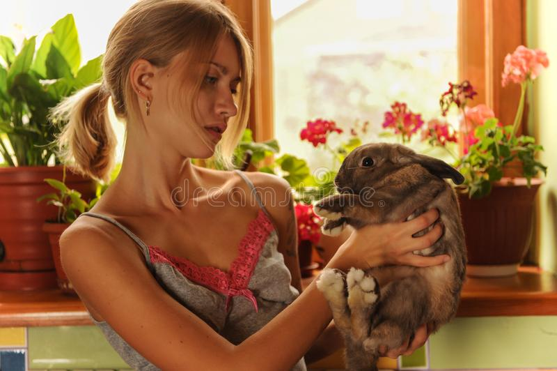 与一张复活节兔子葡萄酒样式照片的友谊从有她的兔宝宝的一个美丽的少妇 库存图片