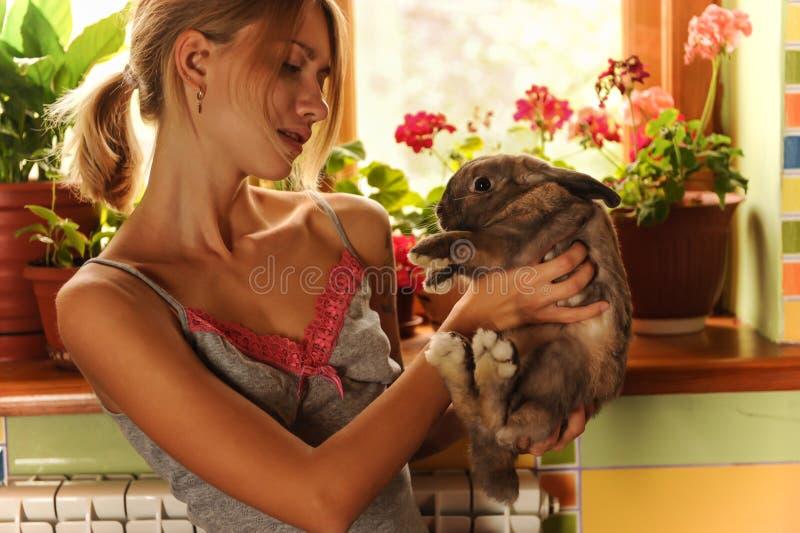 与一张复活节兔子葡萄酒样式照片的友谊从有她的兔宝宝的一个美丽的少妇 免版税库存照片