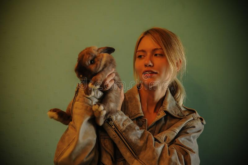 与一张复活节兔子葡萄酒样式照片的友谊从有她的兔宝宝的一个美丽的少妇 免版税图库摄影