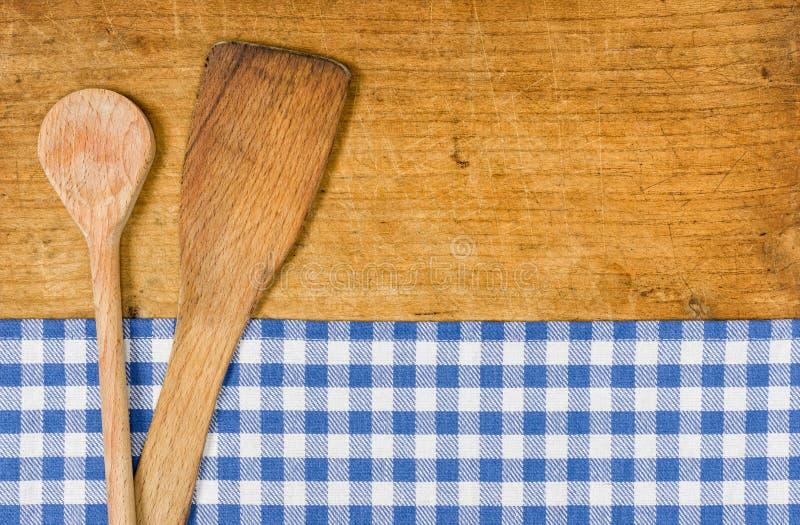 与一张方格的桌布的木背景和木匙子 图库摄影