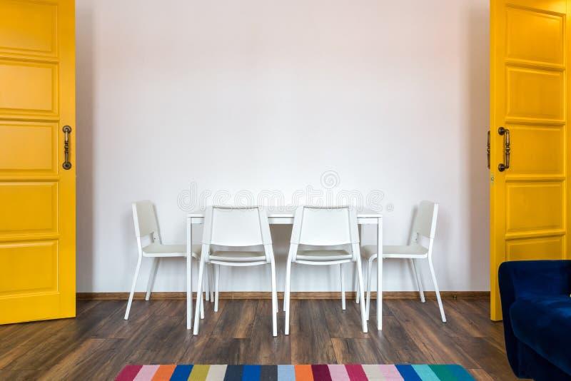 与一张桌的白色木椅子以在内部的白色墙壁为背景与黄色门 免版税库存照片