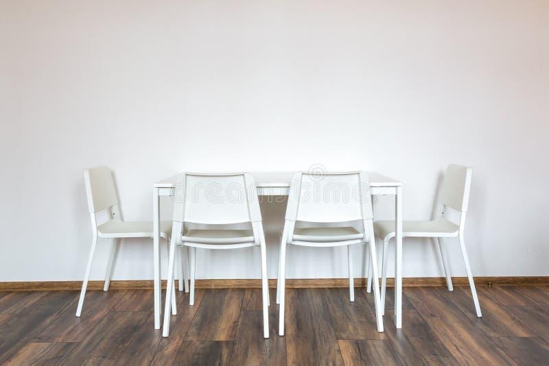 与一张桌的白色木椅子以在内部的白色墙壁为背景 库存图片
