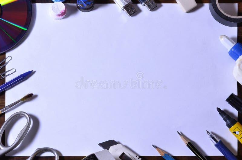 与一张白色空白的纸片的一幅学校或办公室静物画和许多办公用品 学校用品在棕色木头说谎 库存照片