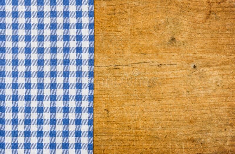 与一张蓝色方格的桌布的土气木背景 库存图片