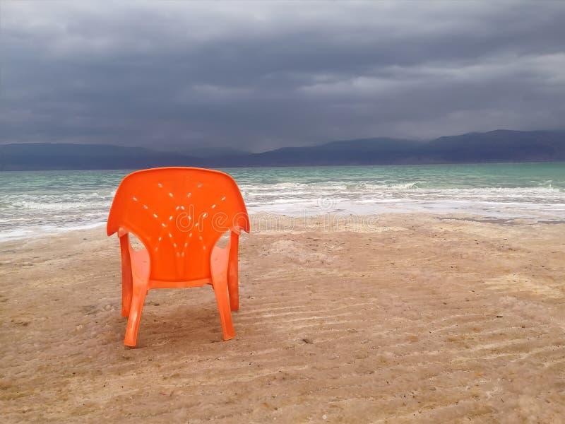 与一把偏僻的橙色椅子的空的海滩在剧烈的深蓝天,死海,以色列下 图库摄影