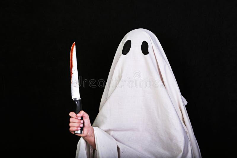 与一把刀子的白色鬼魂在黑背景的血液 万圣节节日晚会 库存照片
