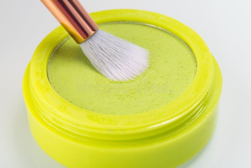 与一把刷子在白色,特写镜头的绿色黄色柔软光滑的眼影膏 库存照片