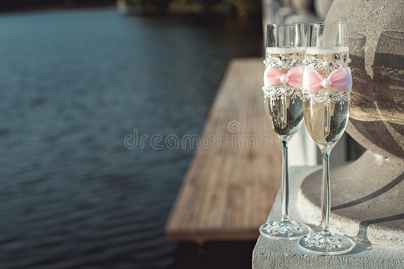 与一把弓的两块婚姻的香槟玻璃在石栏杆 在日落的湖散步 库存照片
