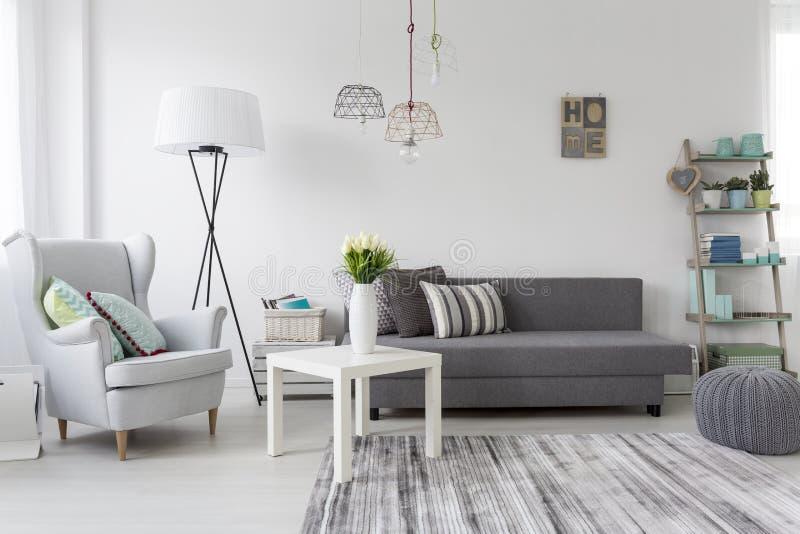 与一把灰色扶手椅子的现代客厅内部 免版税库存照片