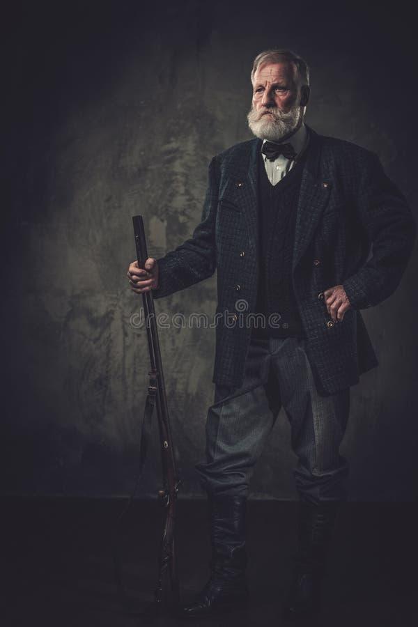 与一把猎枪的资深猎人在传统射击衣物,摆在黑暗的背景 免版税库存图片