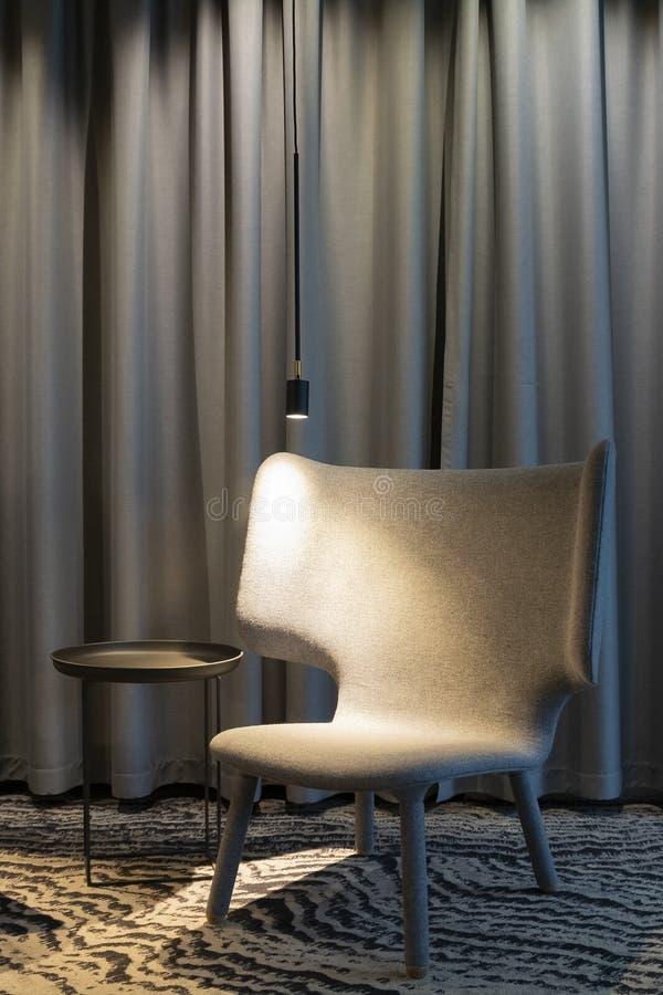 与一把空的舒适的扶手椅子的现代内部有光和桌的在帷幕附近 从右到左方向 免版税库存照片
