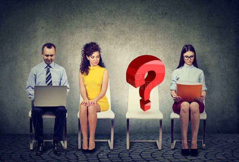 与一把空的问号椅子的人等待的企业工作面试 库存照片