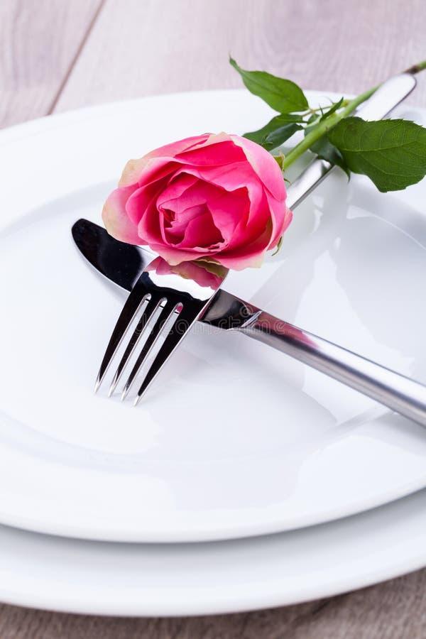 与一朵唯一桃红色玫瑰的表设置 免版税库存图片