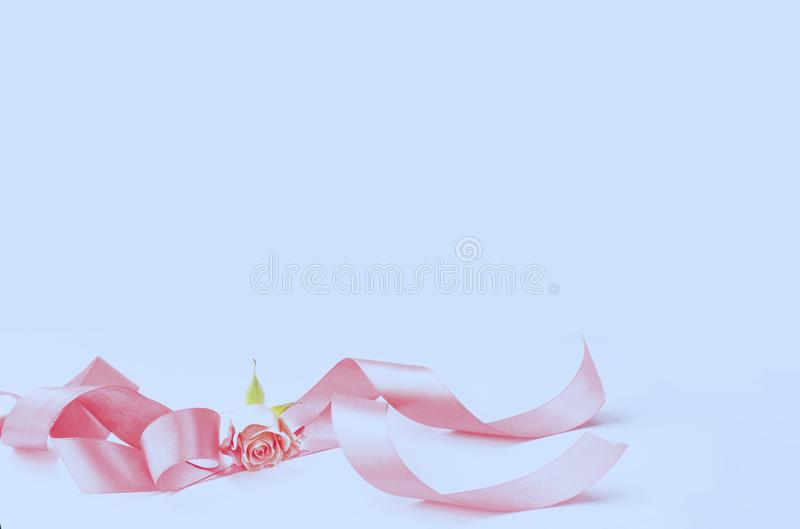 与一朵微型桃红色玫瑰的典雅的丝绸丝带在蓝色背景 免版税库存图片