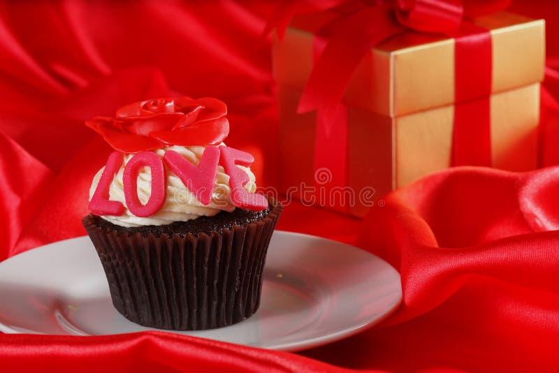 与一朵红色玫瑰的杯形蛋糕在配件箱的顶层和礼品在红色缎b 免版税图库摄影