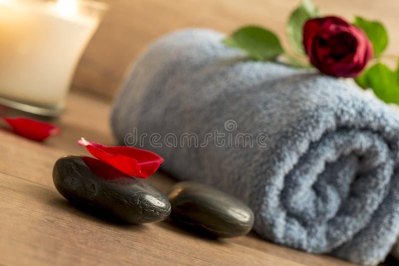 与一朵红色玫瑰的浪漫大气在滚动的毛巾顶部,被点燃 免版税图库摄影