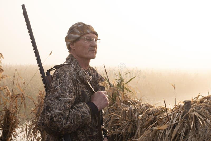 与一杆枪的猎人在湖的黎明长满与芦苇 免版税库存图片