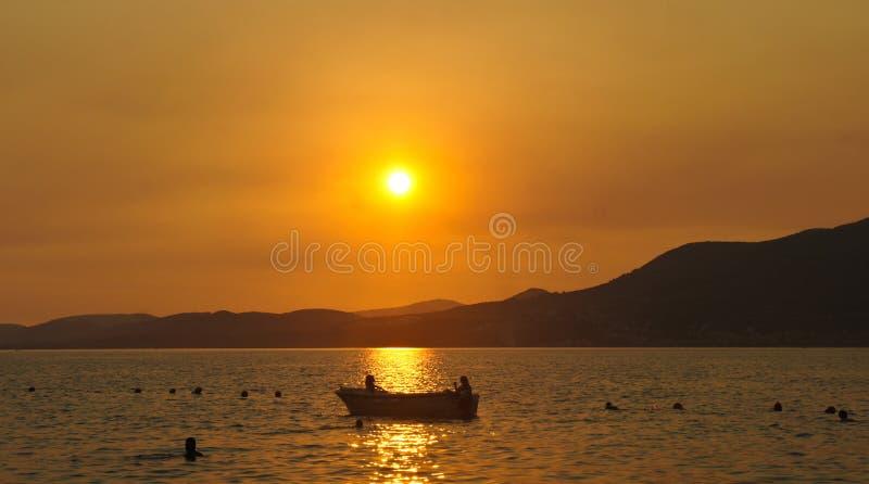 与一条小船的日落在契奥沃岛海岛上的水在特罗吉尔市附近的克罗地亚,达尔马提亚 库存照片
