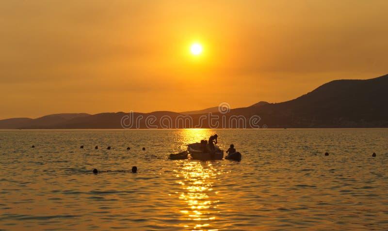 与一条小船的日落在契奥沃岛海岛上的海在特罗吉尔市附近的克罗地亚,达尔马提亚 库存照片