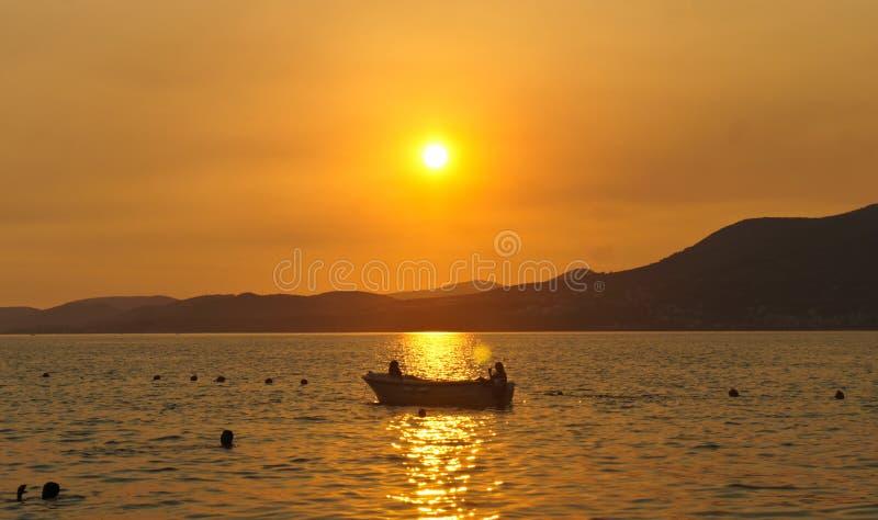 与一条小船的日落在契奥沃岛海岛上的海在特罗吉尔市附近的克罗地亚,达尔马提亚 免版税库存图片