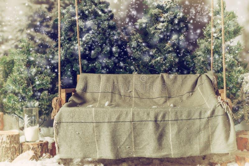 与一条毯子的空的木摇摆在一个积雪的公园或fo 库存图片