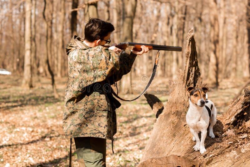 与一条狗的杨猎人在猎人瞄准的森林 图库摄影