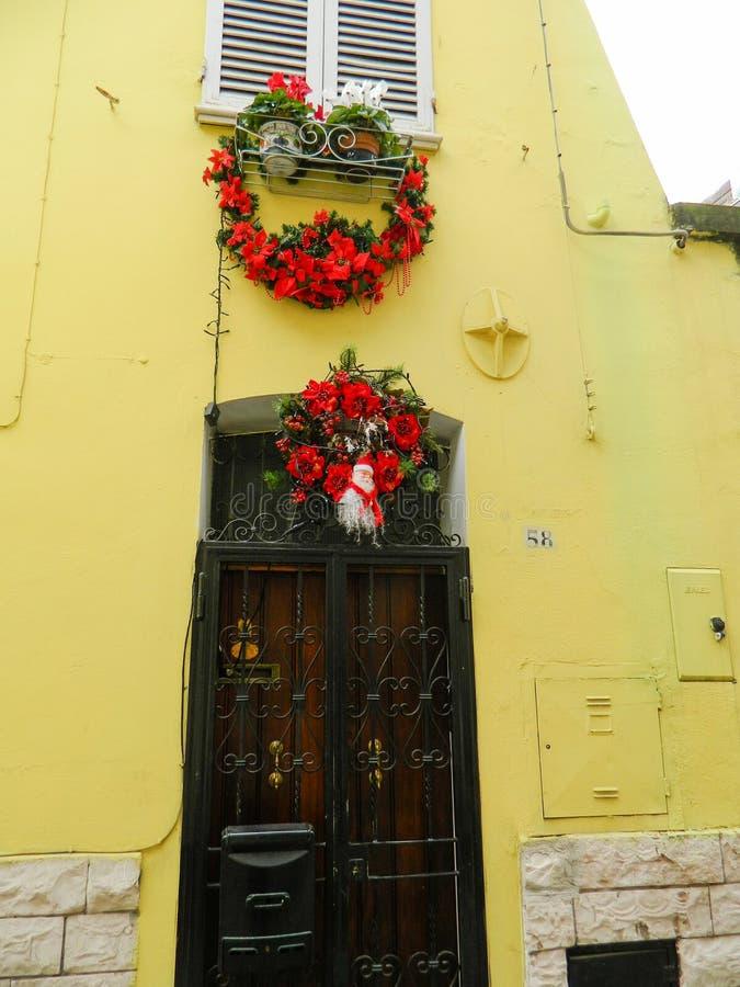 与一条红色丝带的圣诞节花圈在一个棕色木门 圣诞节装饰装饰新家庭想法 免版税库存图片