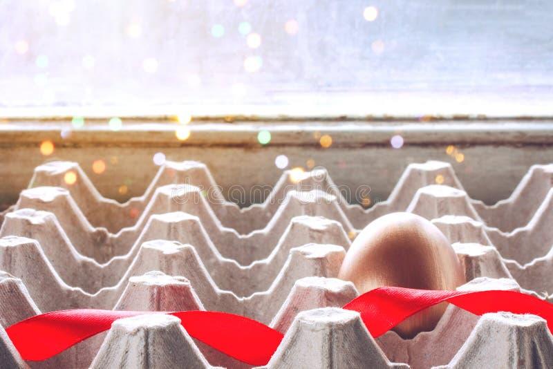 与一条红色丝绸丝带的金黄复活节彩蛋在纸盒箱子 图库摄影