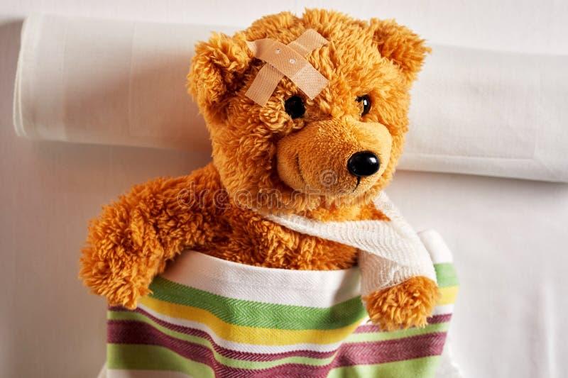 与一条胳膊的逗人喜爱的小的玩具熊在吊索 图库摄影