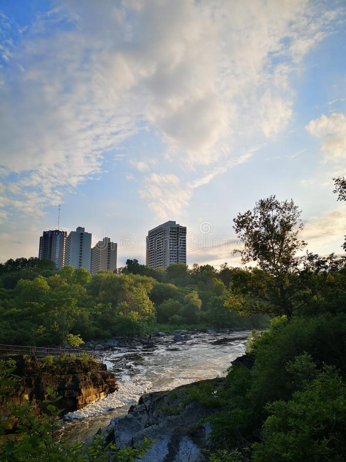 与一条落下的河的城市地平线反对日落 库存照片