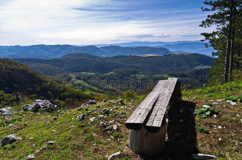 与一条长凳的观点在登上Bobija,周围的峰顶、小山、草甸和五颜六色的森林美丽的景色 免版税库存图片