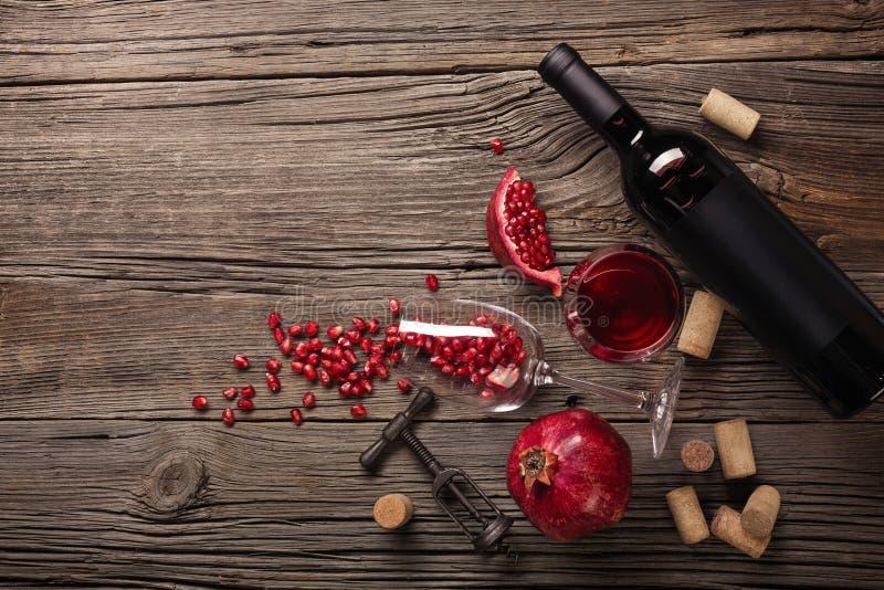 与一杯的成熟石榴果子酒、一个瓶和一个拔塞螺旋在木背景 库存图片
