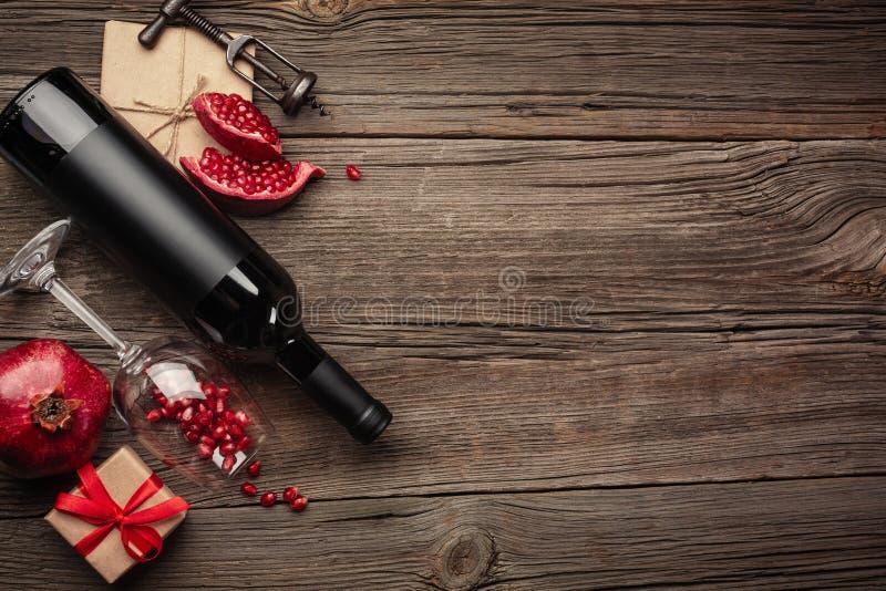 与一杯的成熟石榴果子酒、一个瓶和一件礼物在木背景 与拷贝空间的顶视图 免版税库存照片
