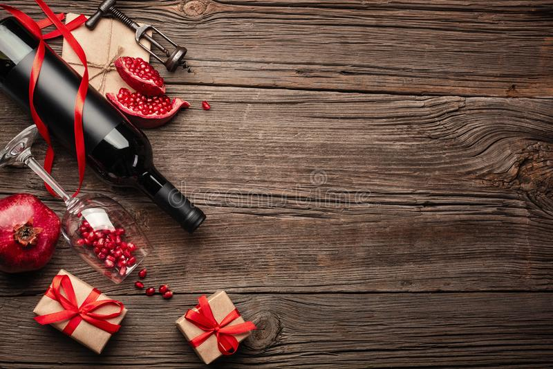 与一杯的成熟石榴果子酒、一个瓶和一件礼物在木背景 免版税库存图片
