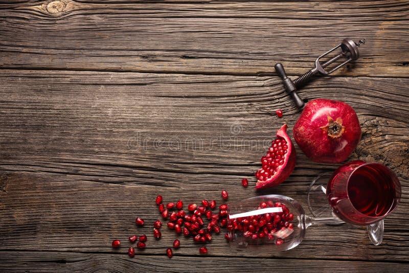 与一杯的成熟石榴果子酒和一个拔塞螺旋在木背景 库存照片