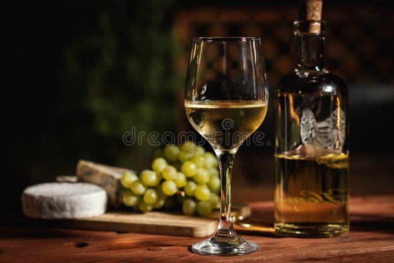 与一杯的浪漫晚餐酒和快餐在一张老木桌上 免版税库存照片