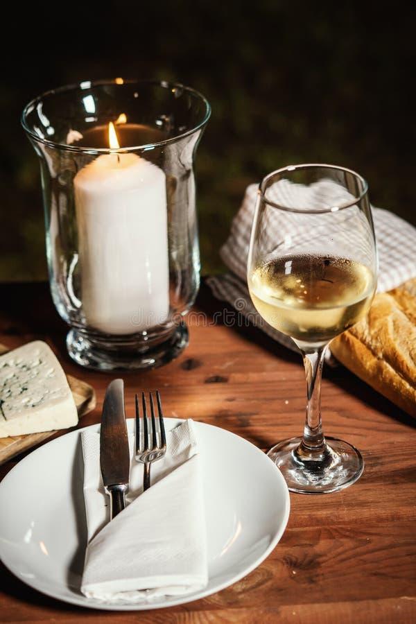 与一杯的浪漫晚餐酒和快餐在一张老木桌上 图库摄影