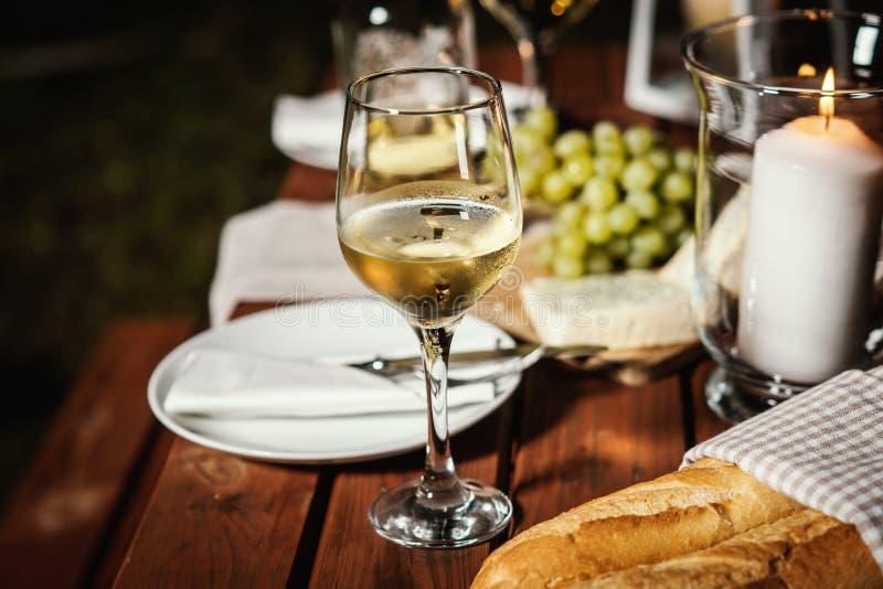 与一杯的浪漫晚餐酒和快餐在一张老木桌上 免版税库存图片