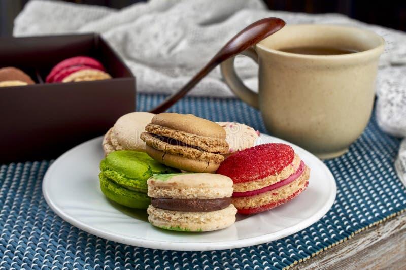 与一杯茶的五颜六色的法国通心面点心 免版税库存照片