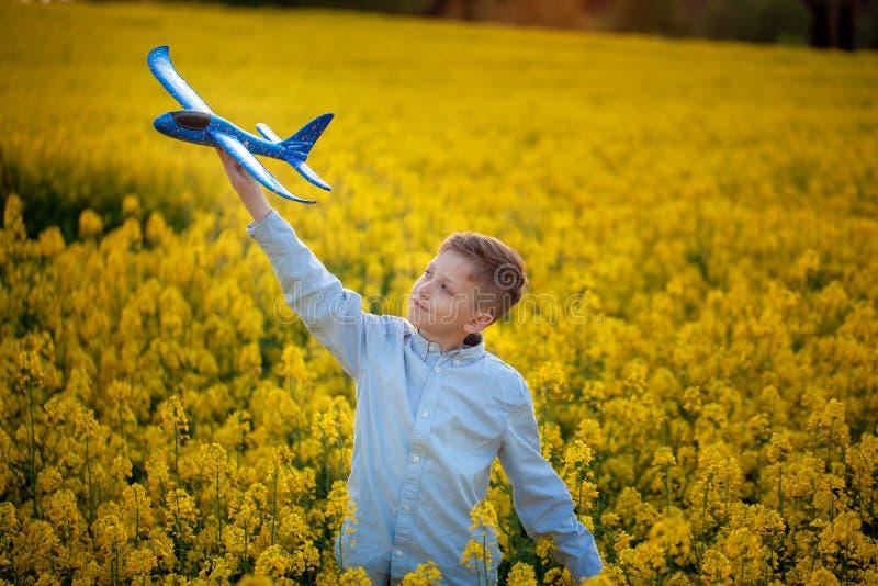 与一架玩具飞机的儿童游戏在旅途日落和梦想在夏日 免版税图库摄影