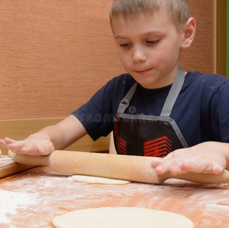 与一根大木滚针的年轻男孩辗压面团,他准备蛋糕 免版税库存图片