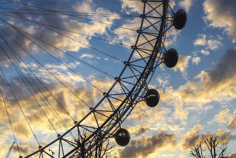 与一棵树的伦敦眼与黄色日落和蓝天 免版税库存图片