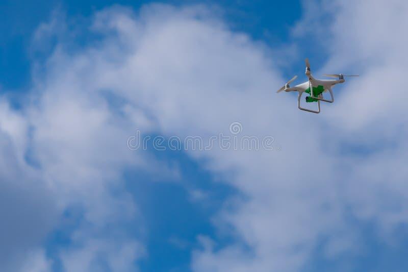与一次绿色照相机飞行的白色寄生虫反对天空 图库摄影