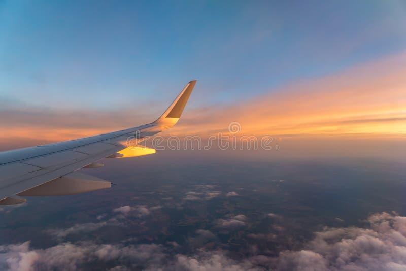 与一次飞机飞行的翼的早晨日出在云彩上的 飞机背景概念地球例证查出surranded移动的白色 库存照片