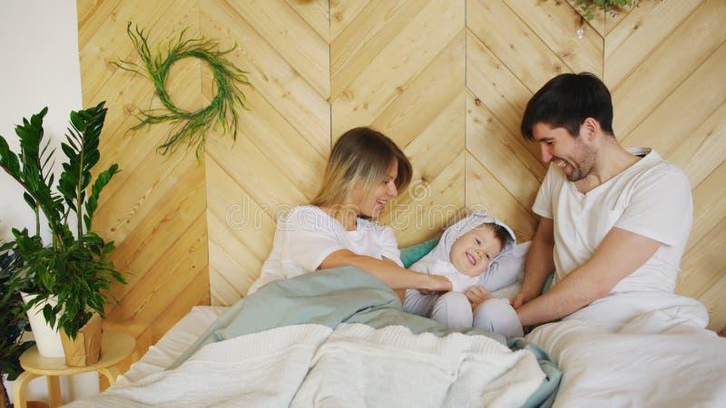 与一点儿子戏剧的一个年轻家庭在床上在卧室 免版税库存图片