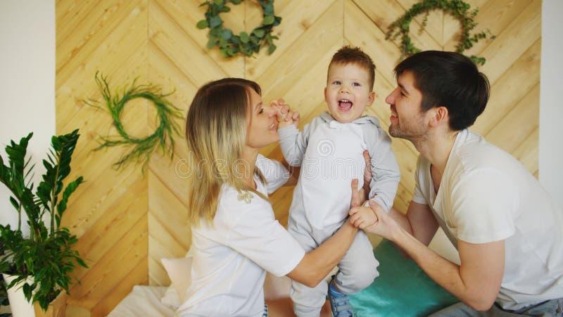 与一点儿子戏剧的一个年轻家庭在床上在卧室 免版税库存照片