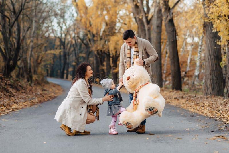 与一点女儿的年轻家庭秋天公园路当前双的 免版税图库摄影