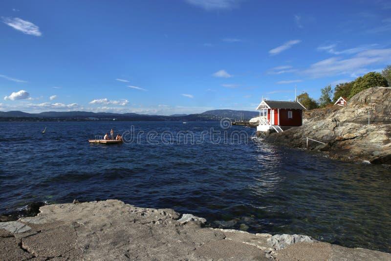 与一点房子的岩石海岸和游泳在海上在内在奥斯陆海湾,挪威 图库摄影