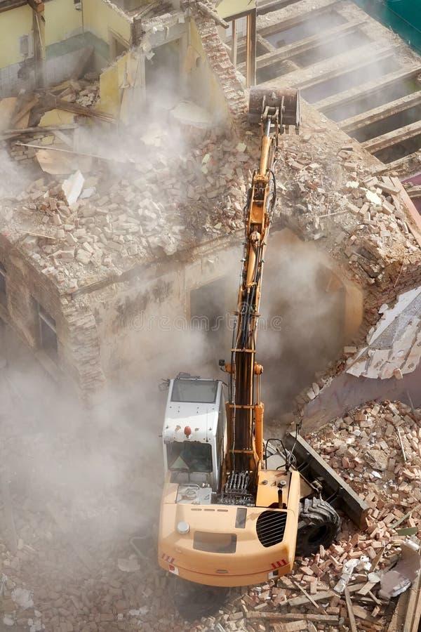 与一种挖掘机的大厦爆破在尘云 免版税库存图片