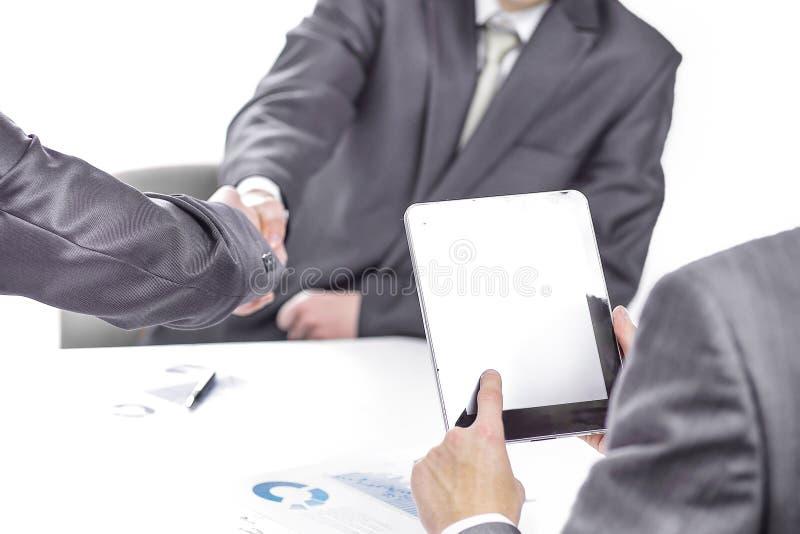与一种数字片剂的商人在商务伙伴握手的背景  免版税库存照片